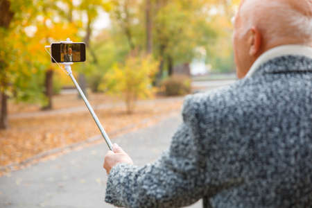 An elderly man does selfie on a mobile phone with a monopod.