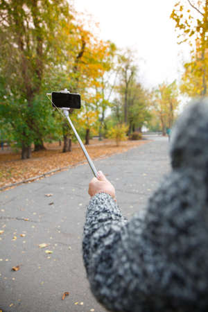 The hand of an elderly man who holds a monopod with a mobile phone.