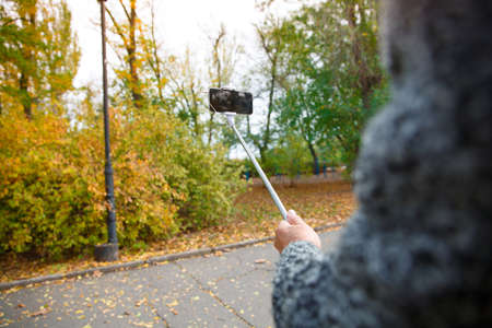 A mans hand holding a mobile phone with a monopod in a warm park.