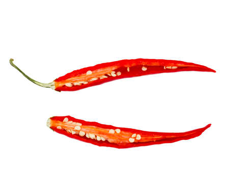 Cut red halved red pepper with seeds close-up on a white isolated background