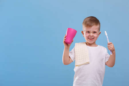 A joyful boy with a toothbrush and a cup on a blue background Banco de Imagens