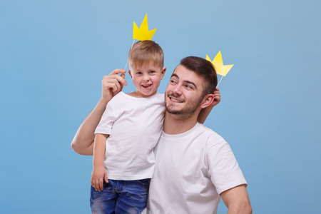 Dad and his son put each other crown on a blue background 스톡 콘텐츠