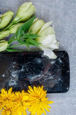 A broken touch and stylish phone lies horizontally between the flowers yellow and white on a stone background