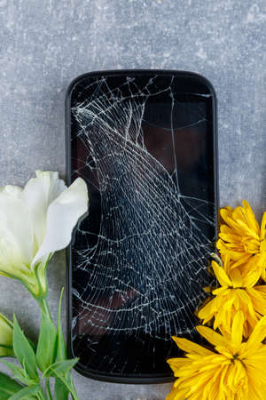 A broken touch and stylish phone rests vertically between flowers of white and yellow close-up on a stone background
