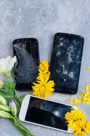 Broken touch and stylish phones next to flowers white and yellow with petals on a stone background. View from above