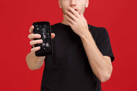 A guy holds a broken modern mobile phone and covers his mouth with a hand from fright.