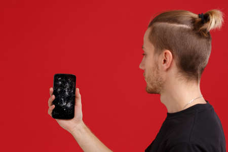 A serious European guy holding a broken mobile phone and looking at him. Stock Photo
