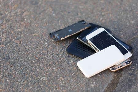 Several broken smartphones are on the asphalt.