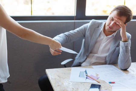 A man, holding a document, which he gives the girl an office worker. Indoors in the office. Imagens