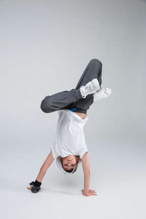 An active boy dances to break dance stands on his hands bending both legs in his lap.