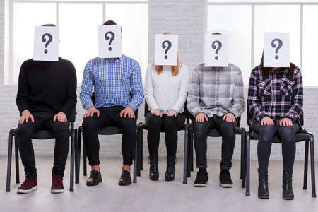 A group of guys and girls are sitting in line with paper on their faces with a question mark. Indoors. Stockfoto
