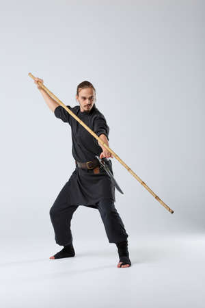 A ninja man is practicing fighting with a bamboo fighting stick.