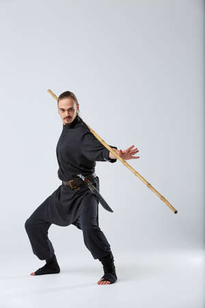 An experienced fighter man, works out a combat movement with a long bamboo fighting stick. Stock Photo