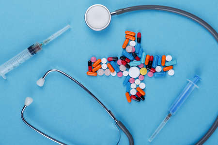 On a blue background, there is a layout of medical preparations and instruments, a doctors stratoscope, a syringe and a bunch of different tablets lined in the form of a cross. View from above.