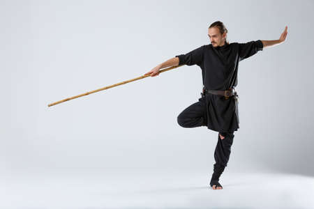 An experienced fighter, stands in a fighting posture with a fighting bamboo stick.