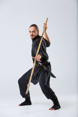 The artful fighter in a black suit, fighting with a long bamboo fighting stick. Stock Photo