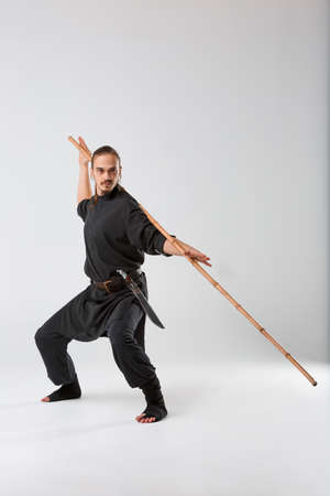 A man, in a black kimono is practicing martial arts technique with a long bamboo fighting stick.