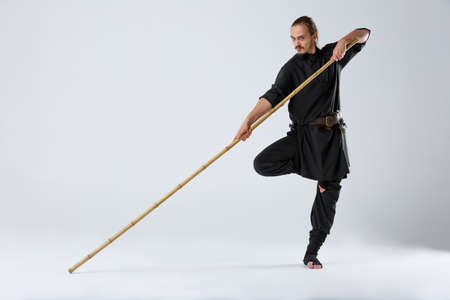 A fighter in a black kimono, stands in a fighting artificially pose on one leg and holds a bamboo stick. Stock Photo