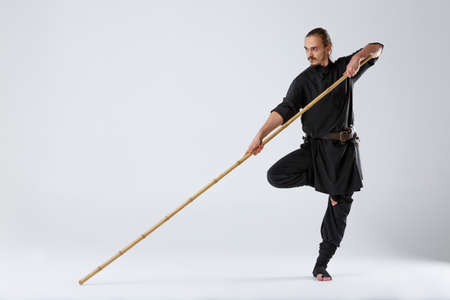 A ninja man in a black kimono, standing in a fighting posture on one leg and holding a fighting stick.