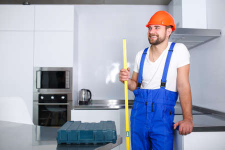 Happy builder, in uniform and helmet stands in the kitchen, smiling and holding a waterpas in hands.