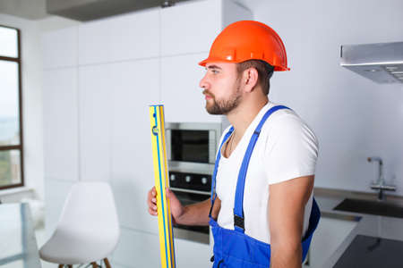A male builder, in uniform, stands sideways, looks into the distance and holds a waterpas in his hand.