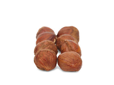 A bunch of useful kernel hazelnuts in the shell are laid out exactly in two rows. Close-up. Isolated on white background. Banco de Imagens