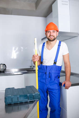 A happy construction worker, in uniform, holds a waterpas in his hand. Stockfoto