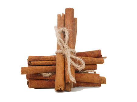 Several sticks of cinnamon sticks are wrapped in a sack thread. Close-up. Isolated on white background.