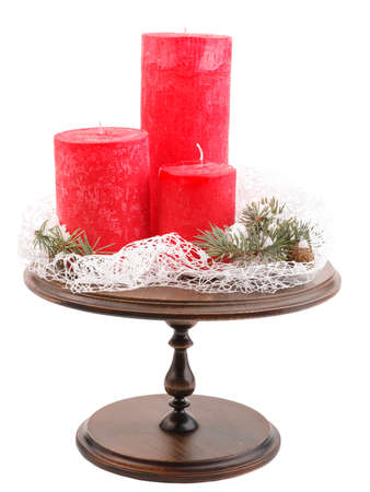 Three red Christmas candles of different sizes and fir-tree branches with cones on a wooden crucible. Isolated on white background.