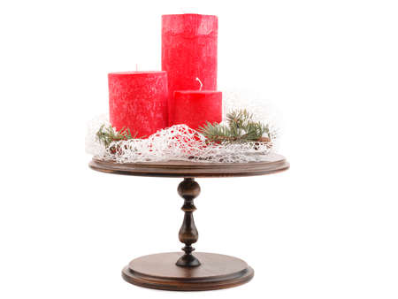 On a round wooden countertop, three festive red Christmas candles of different sizes and Christmas trees with cones. Christmas decoration. Isolated on white background. Stock Photo