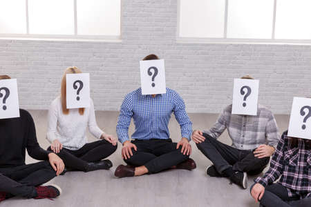 A group of five people sit on the floor, on their faces are sheets with a question mark.