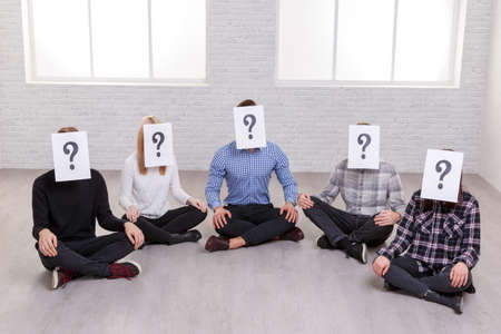 A group of people are sitting on the floor, on their faces are paper sheets with a question mark,. Stock Photo