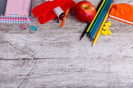 On the wooden surface are notepads, colorful pencils, a stapler and a toy airplane. Place for the inscription. Stockfoto
