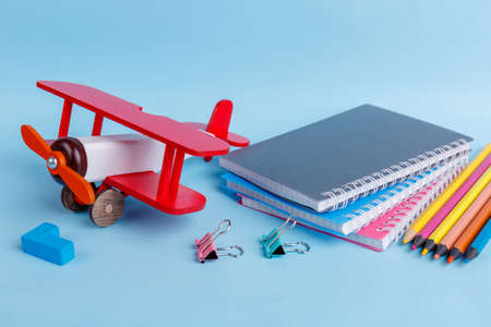 Notebooks, clips, colored pencils, chalk and a wooden toy airplane are located on a blue background. Stock Photo
