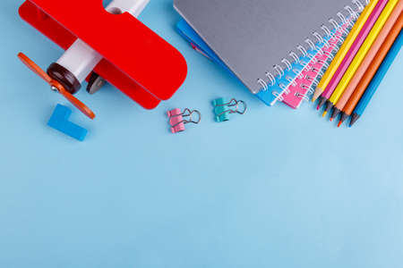 On the blue background are notebooks, clips, colored pencils, a chalk and a red toy airplane. Top view.