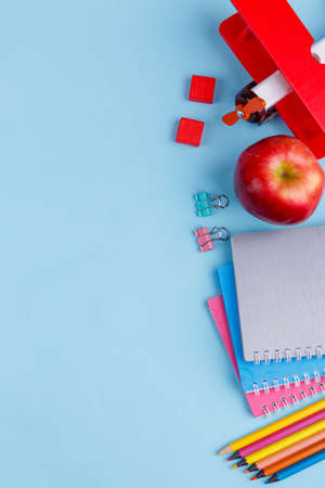 Arrangement of notebooks, paper clips, pencils, red wooden airplane and apple.
