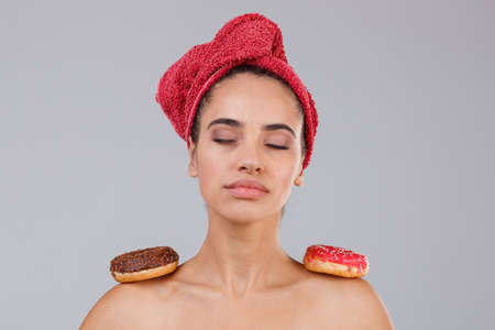 A calm girl with a towel on head and donut on her shoulders closed her eyes. On a gray background. Stock Photo