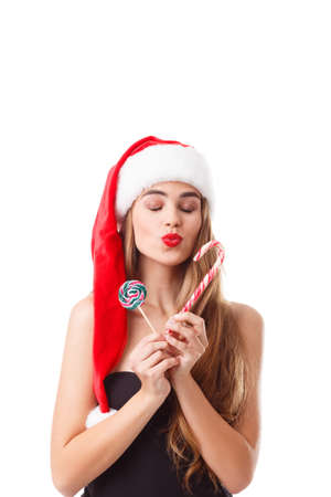 A young girl in a Santa hat, holding Christmas candies and sending an air kiss with her eyes closed. Isolated.