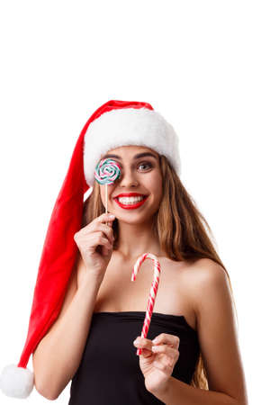 A happy young girl in a Santas hat, holds Christmas candiesand one of them closes her eyes. Isolated .