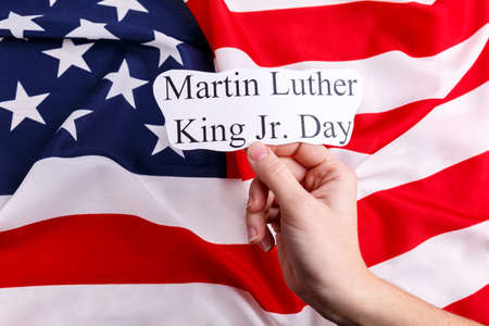 A mans hand holds a paper with inscription Martin Luther King Jr. Day, against the background of the American flag. Stock Photo