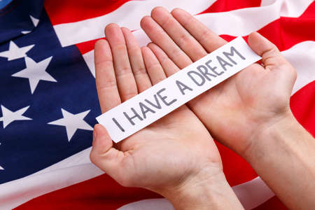 Hands of a man holding a sign with the inscription I have a dream. Against the background of the American flag. Stock Photo