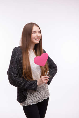Pretty girl holding a pink heart on a stick, smiling and looking away. Isolated on white. Foto de archivo