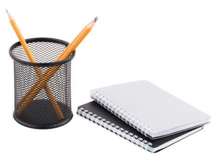 Two black and gray notepad with spiral binding of sheets and next black container in a mesh with three sharp pencils of orange inside. Isolated on white background. Close-up. Stock Photo
