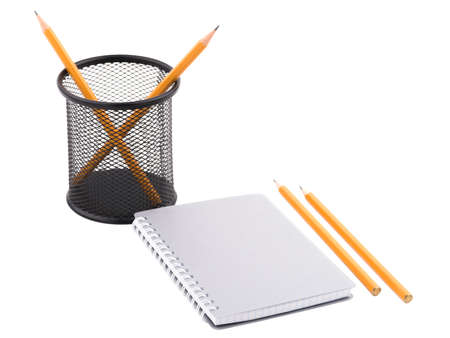 Notepad with spiral binding of sheets and two sharp pencils of orange color and a black container in a mesh with pencils inside. Isolated on white background. Close-up. Stock Photo