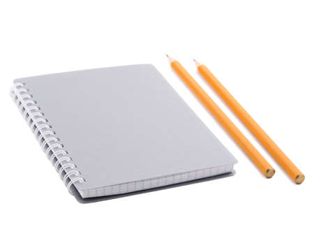 A gray notepad with spiral binding of sheets and two sharp pencils of orange color. Isolated on white background. Close-up.