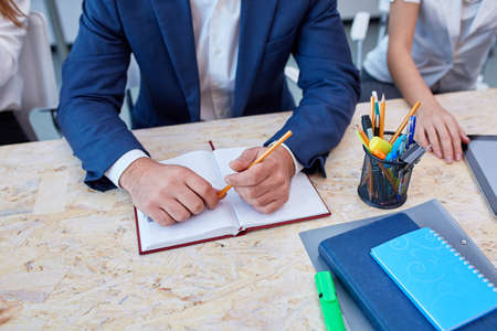 Hands of a man in a suit is sitting at desk and holding an pencil next to a notepad.
