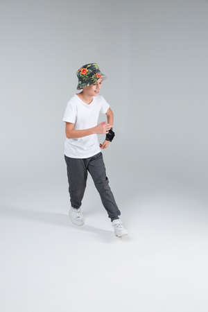 A teenage boy dances stepping in front and actively moving his hands. Stock Photo