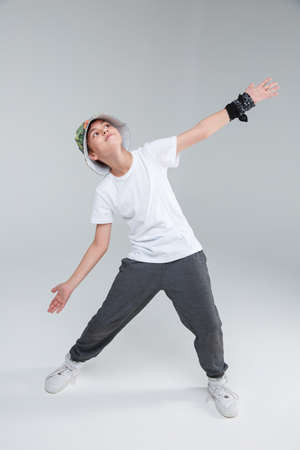 A young boy dancing standing standing with arms and legs wide apart and look up. Stock Photo