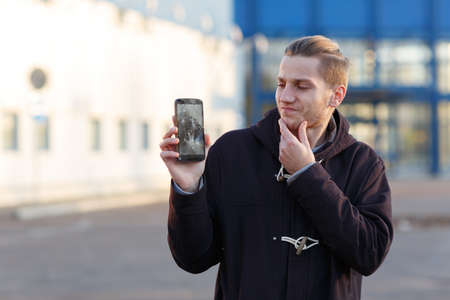 A young guy, holding a mobile phone with a broken screen, frustratedly rubbing his chin.