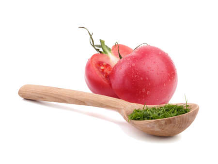 Bright red tomatoes with a wooden spoon full of dill isolated on a white background. Ripe, juicy and organic cherry tomatoes. Healthy vegetables.